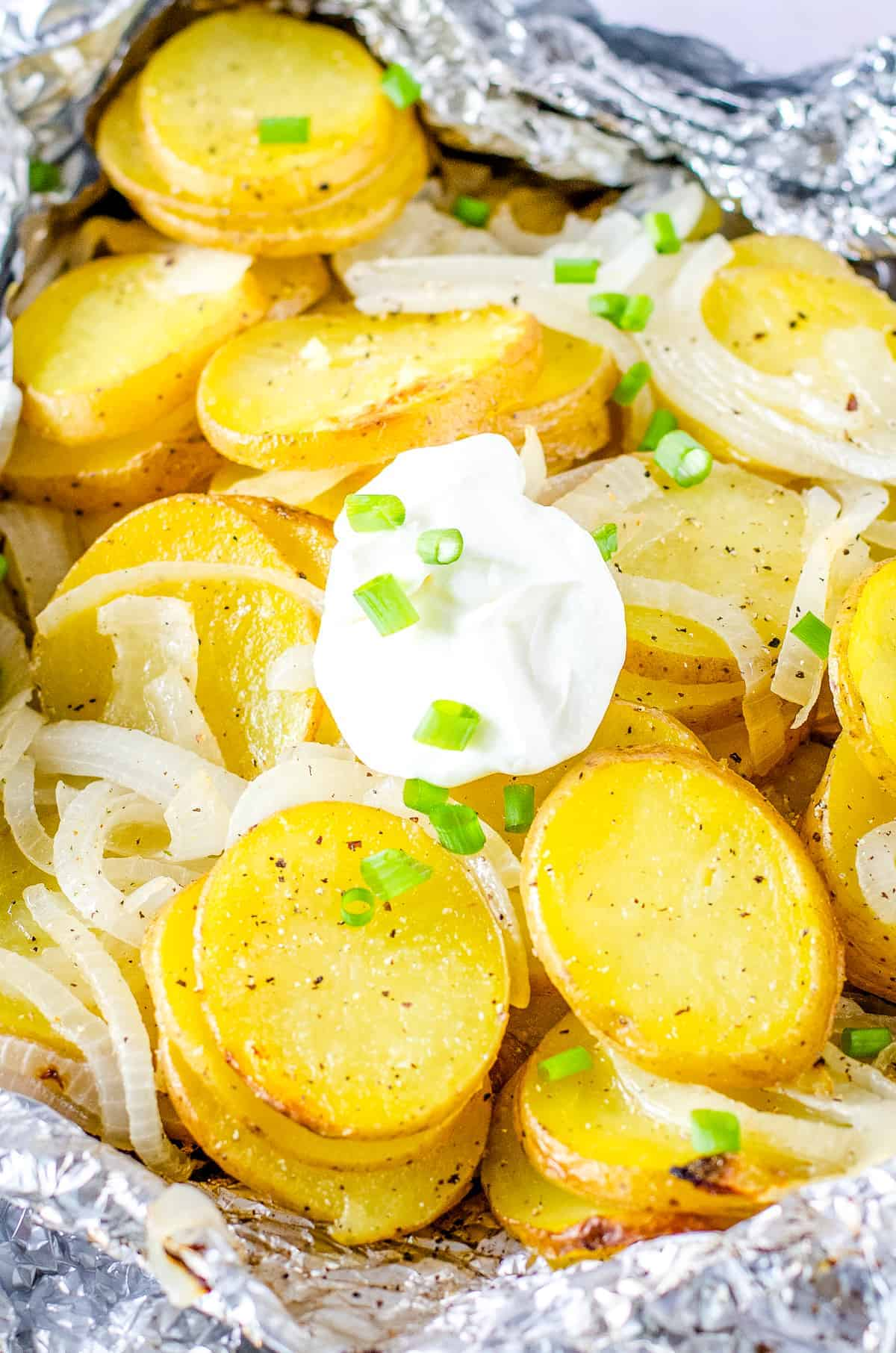 Foil Packet with potatoes and onions topped with sour cream dallop