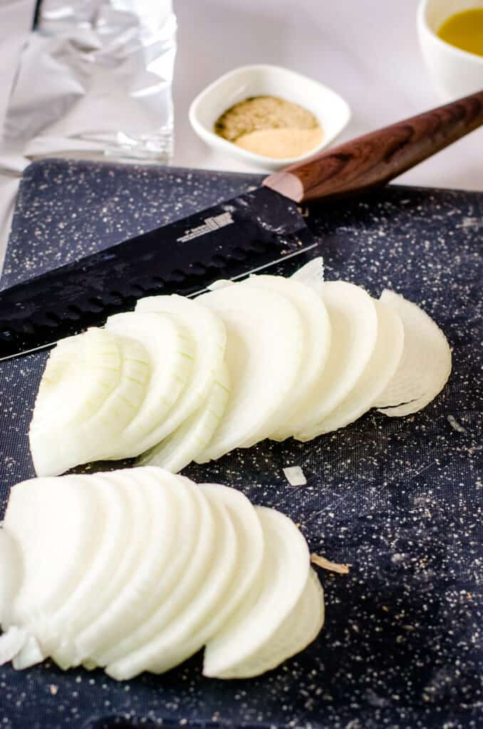 Thinly sliced onions on cutting board