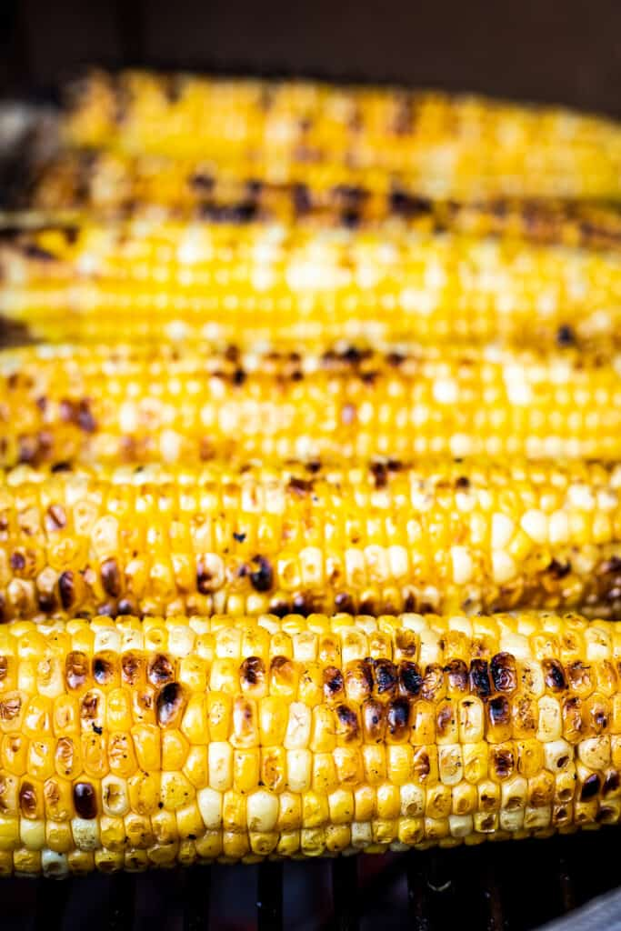 Charred Corn on the cob laying on grill grates