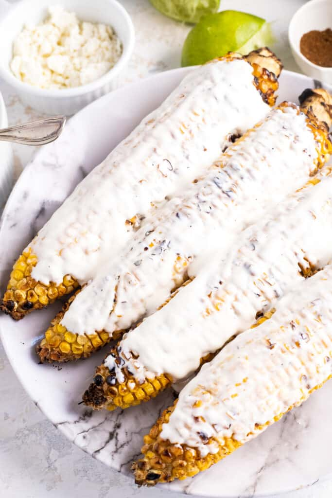 Charred corn on the cub topped with creamy sauce