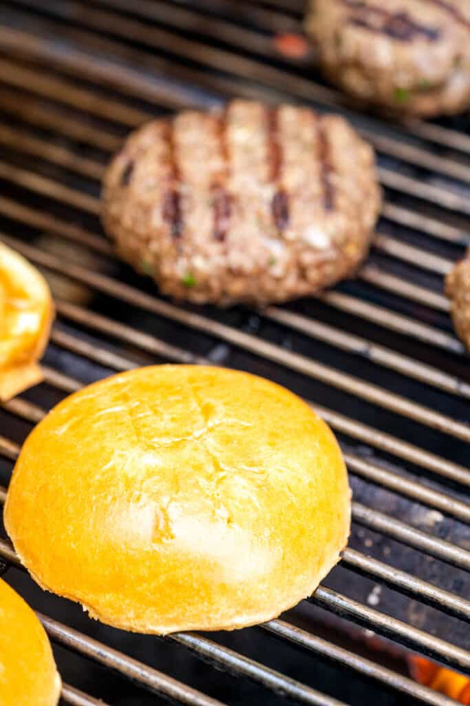 Grill grates with bun tops and burgers