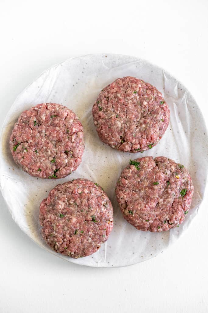 Four beef patties on plate