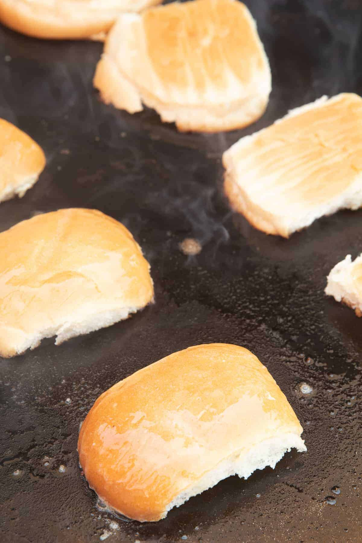 Buttered buns being toasted on griddle