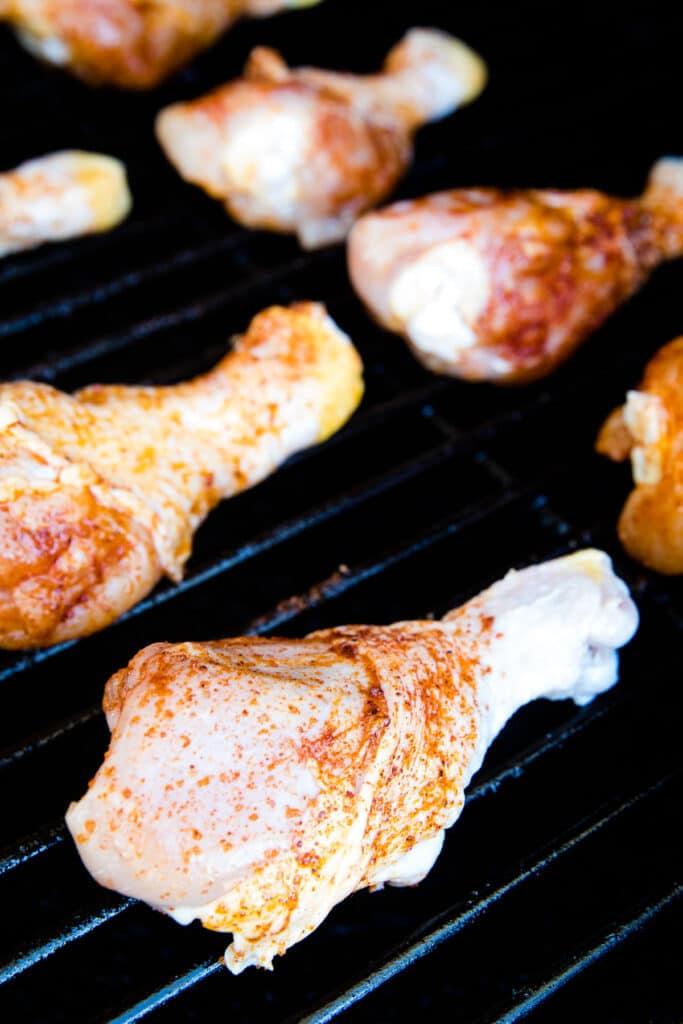 Seasoned chicken legs on smoker grates