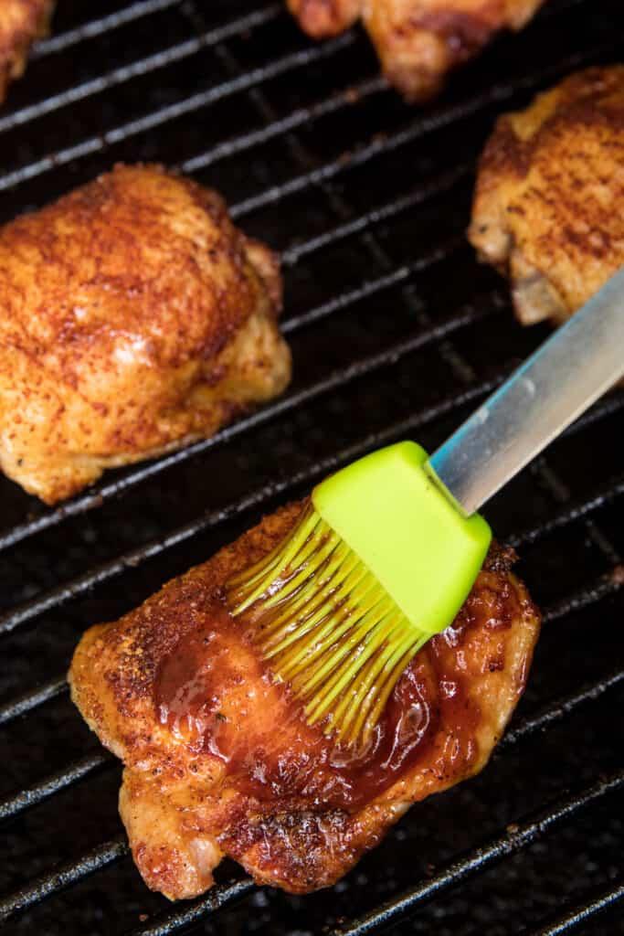 Basting brush spreading BBQ sauce on chicken thighs