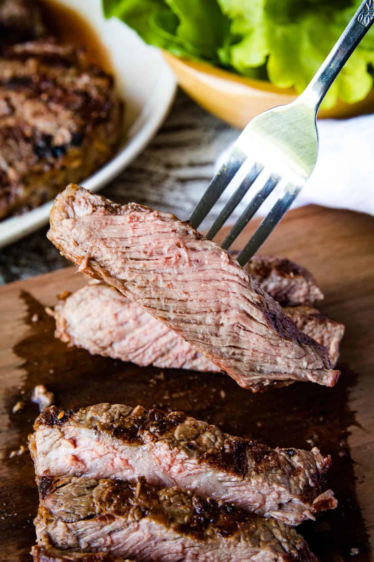 Fork holding piece of ribeye steak
