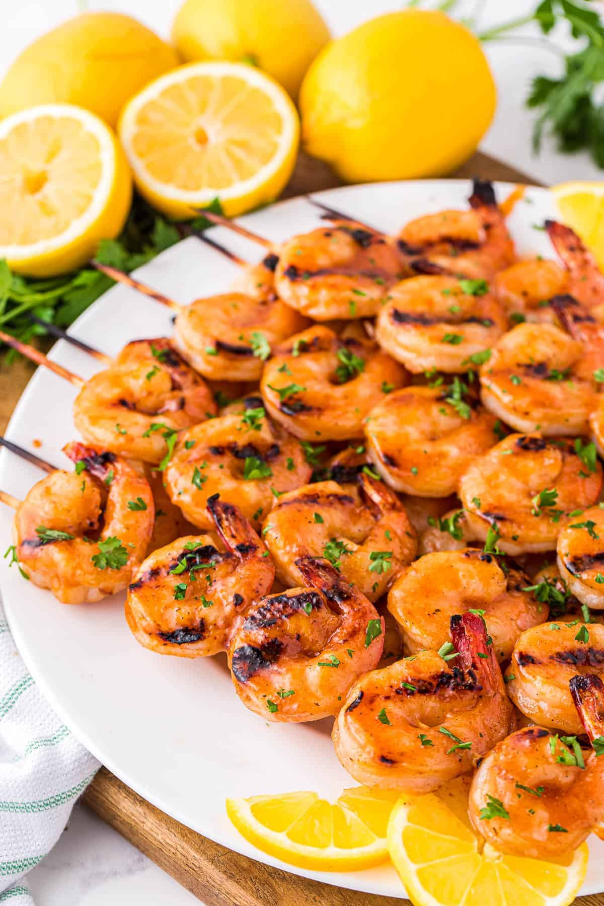 White plate with spicy grilled shrimp skewers on it